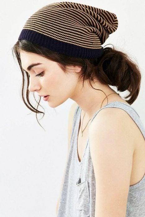Chica de cabello castaño con una coleta utilizando un gorro de invierno
