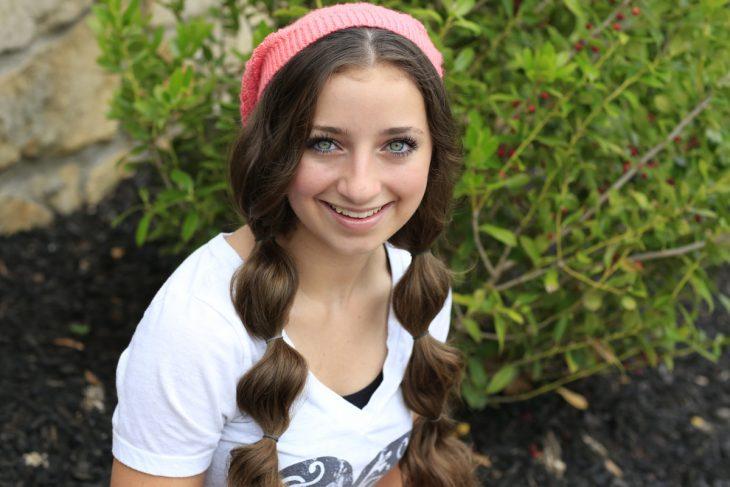 Chica de cabello castaño peinado con dos coletas usando un gorro de invierno