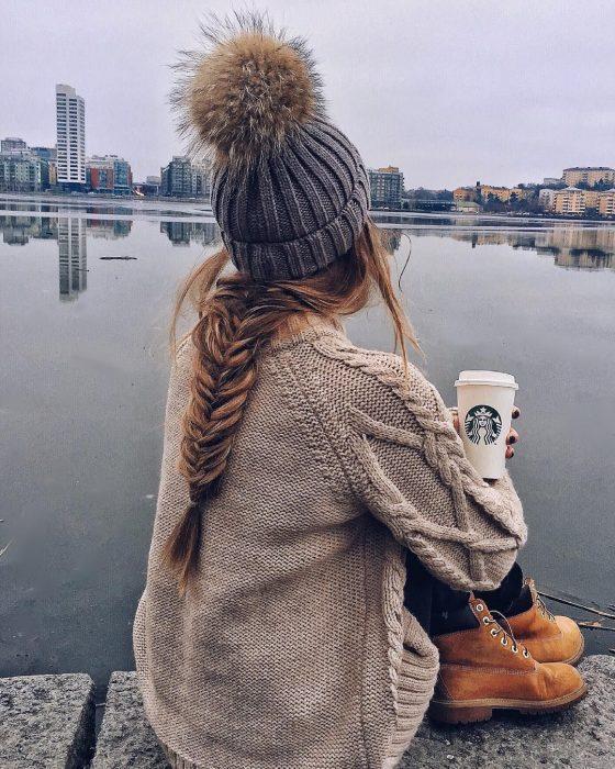 Chica de cabello largo y trenzado usando gorro de invierno sentada y bebiendo café