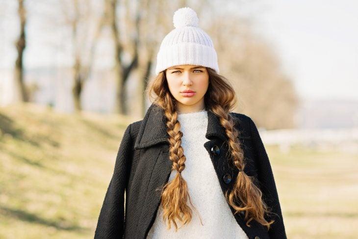 Chica con cabello largo y trenzado vistiendo un gorro blanco d e invierno y un abrigo negro