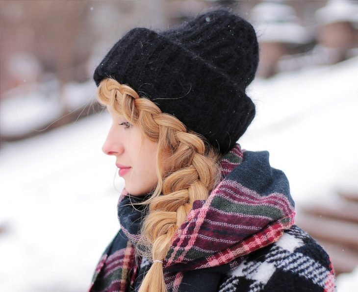 Chica de cabello rubio trenzado con gorra negra para invierno