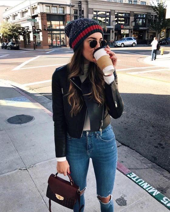 Chica de cabello castaño y largo con gorra de invierno tomando un café