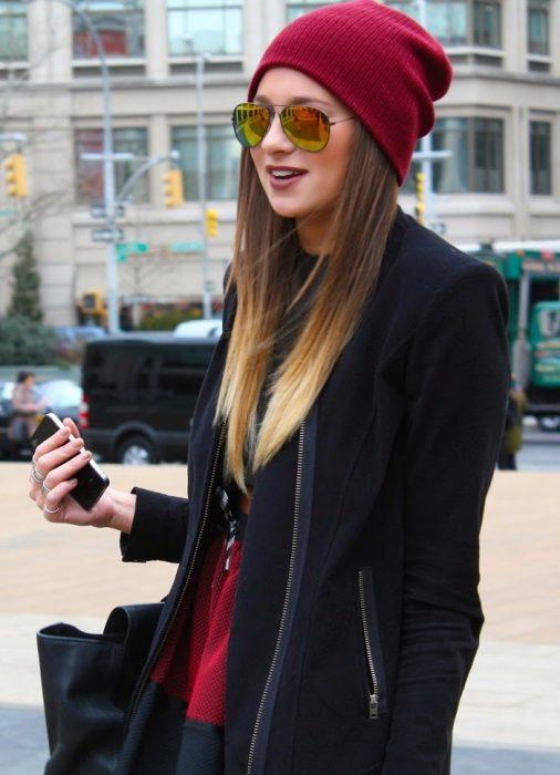 Chica con cabello lacio usando una gorra roja de invierno