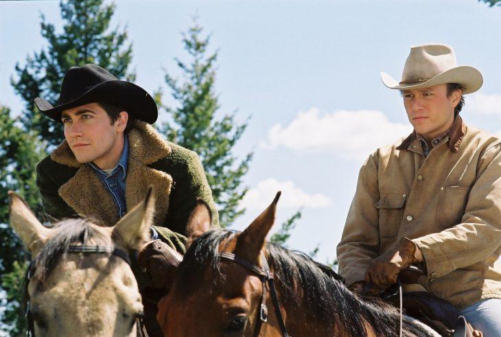 hombres vestidos de vaqueros paseando a caballo