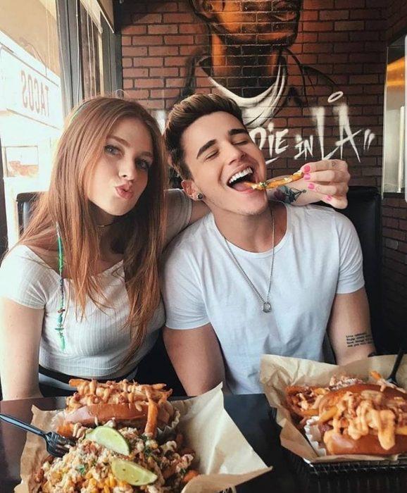 Pareja feliz comiendo papas en un restaurante