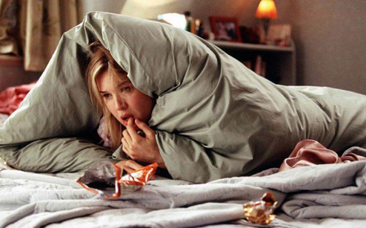 Mujer triste envuelta en una cobija mientras come chucherías