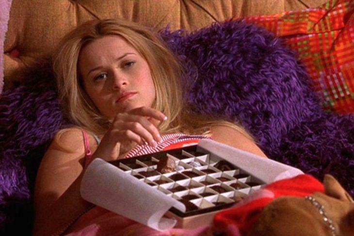 Mujer rubia triste comiendo chocolates