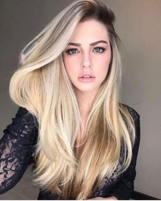 Chica con el cabello teñido de rubio con raíz de color negra