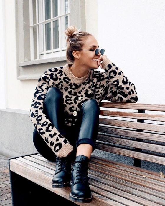 Chica feliz con suéter de animal print sentada en una banca de madera