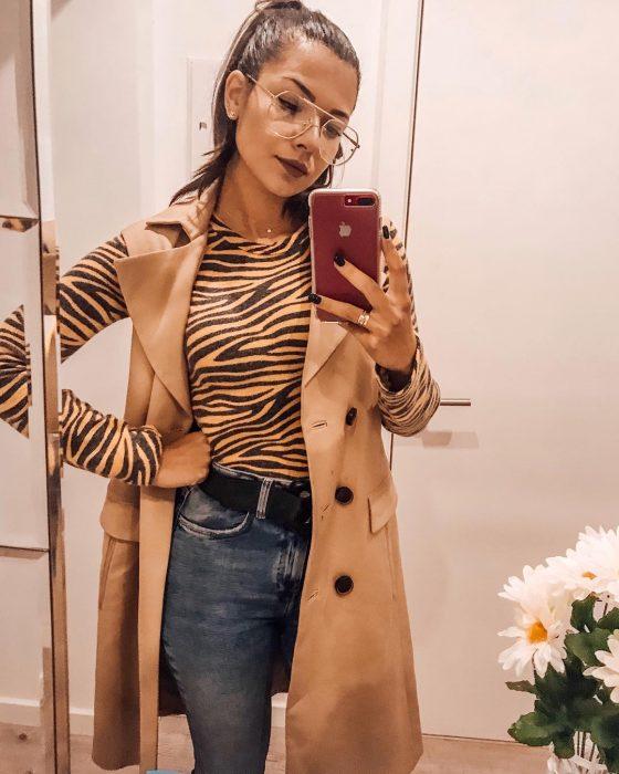 Chica con blusa de animal print tomándose selfie frente al espejo