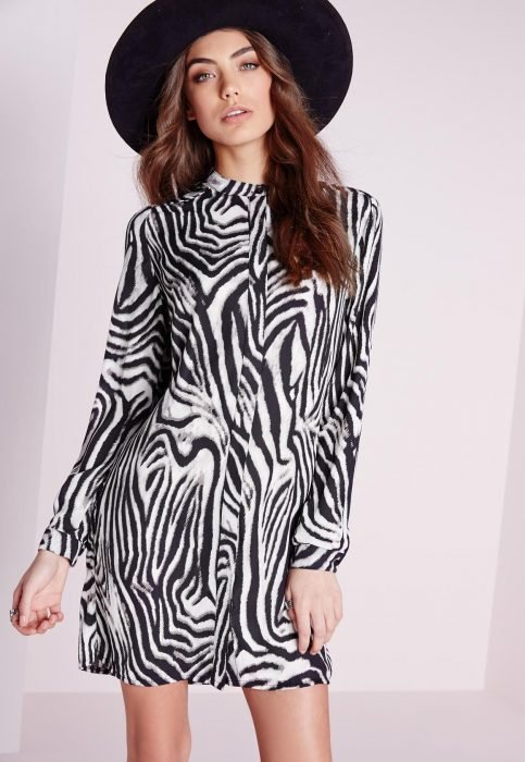 Chica pelirroja usando un vestido de animal print de cebra y un sombrero negro