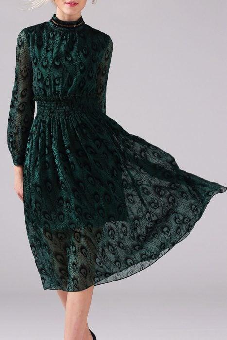 Chica modelando un vestido verde con animal print de pavoreal