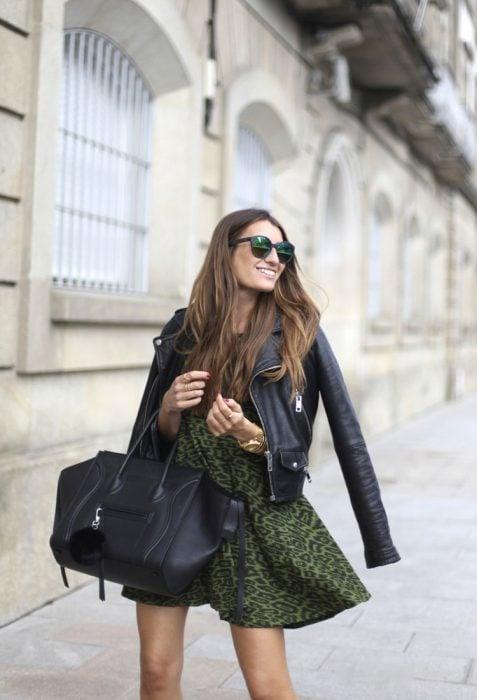 Chica joven usando un vestido verde de animal print, lentes oscuros y bolsa negra de mano