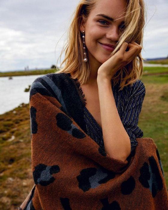 Chica rubia y feliz con chal de animal print