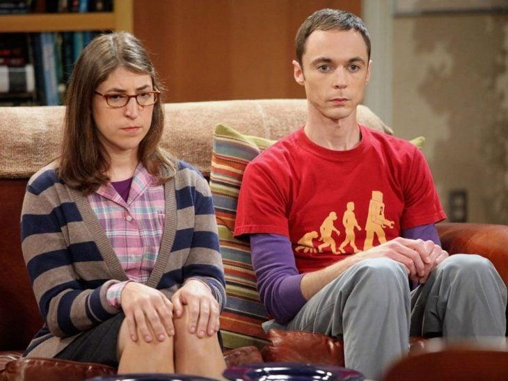 Pareja de novios nerd sentada en un sillón en medio de un silencio incómodo