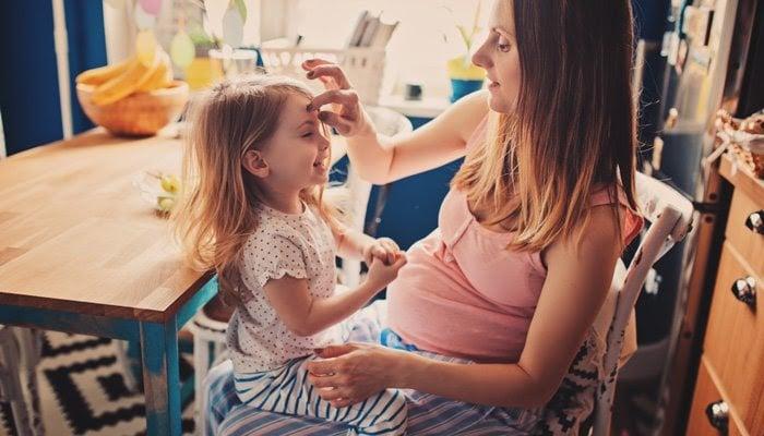 Mamás sentada con hija en su regazo mientras ambas sonríen
