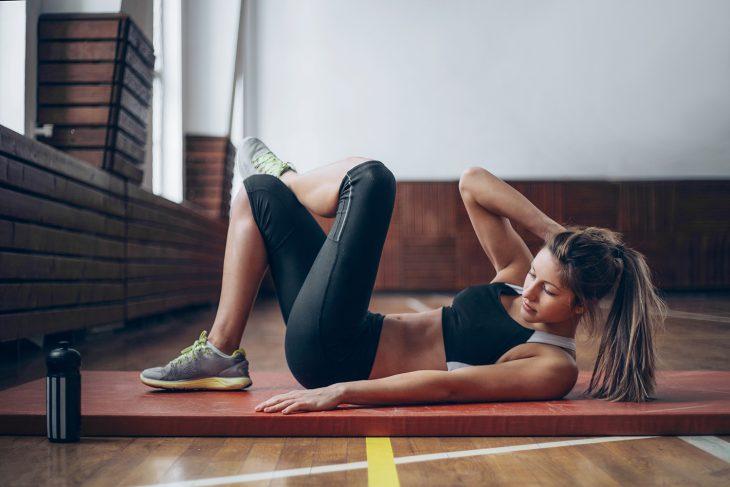 Mujer joven haciendo abdominales con ropa deportiva