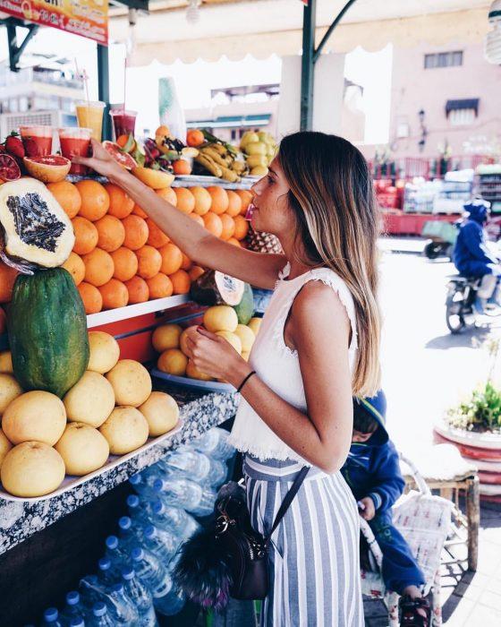 Chica joven en el mercado comprando jugos naturales y frutas