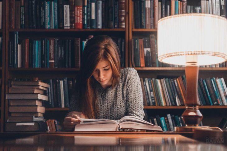 Chica joven leyendo un libro en la biblioteca