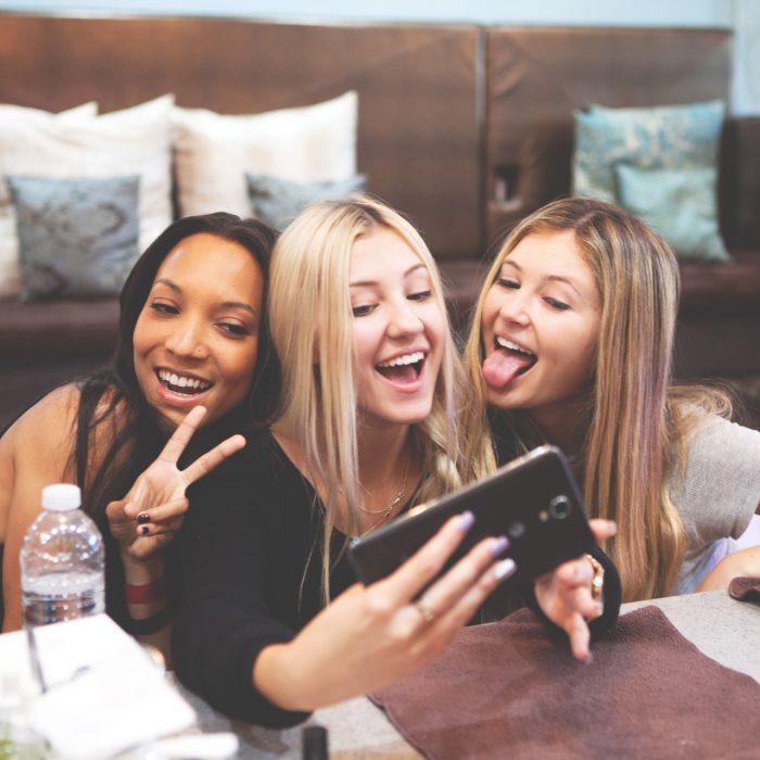 Grupo de tres amigas sonriendo mientras se toman una foto con el celular