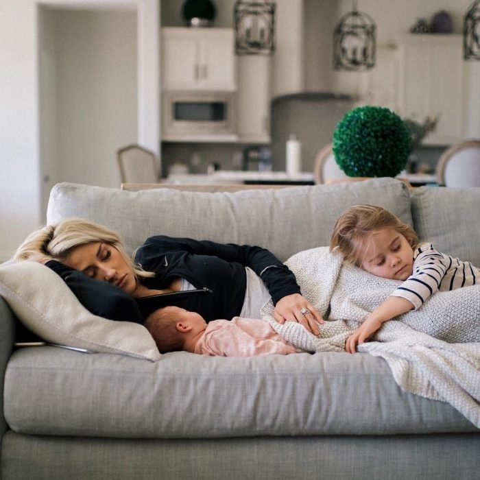 Mujer dormida en el sillón con sus dos hijos pequeños