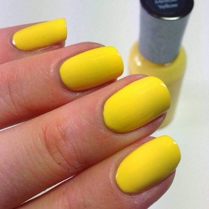 manos de mujer con uñas color amarillo