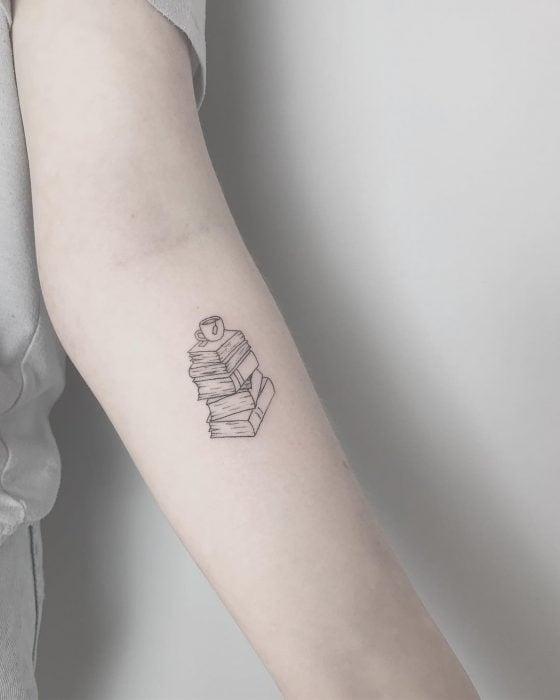 Chica con un pequeño tatuaje de libros en su brazo