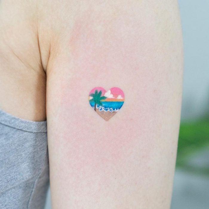 Chica con un tatuaje de un corazón que tiene una playa dentro