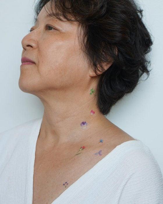 Chica con un tatuaje de un unas flores en su cuello