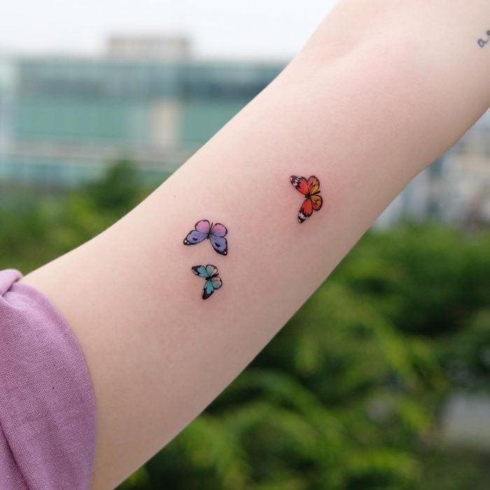 Chica con un tatuaje de tres mariposas de diferentes colores