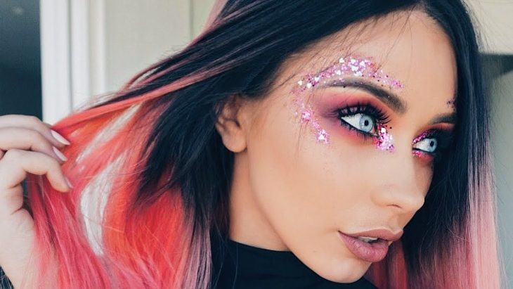 mujer con maquillaje de brillos en la cara
