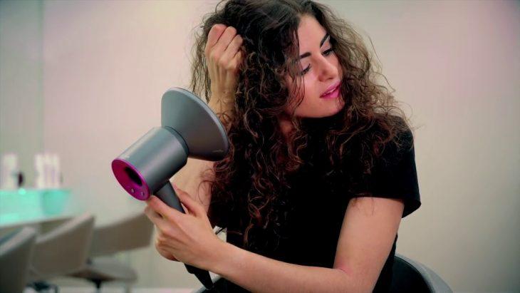 Chica de cabello chino secándolo con una secadora con difusor