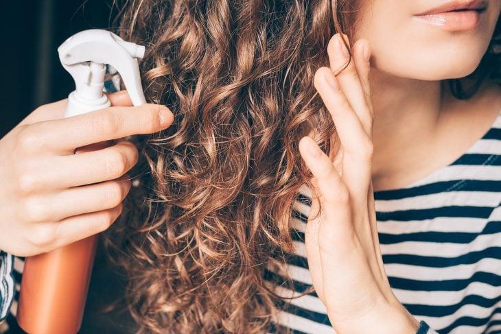 Chica aplicando tratamiento en su cabello chino