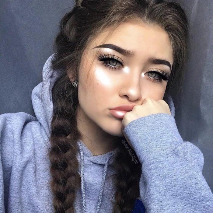 Chica de cabello chino con dos tranzas a los lados