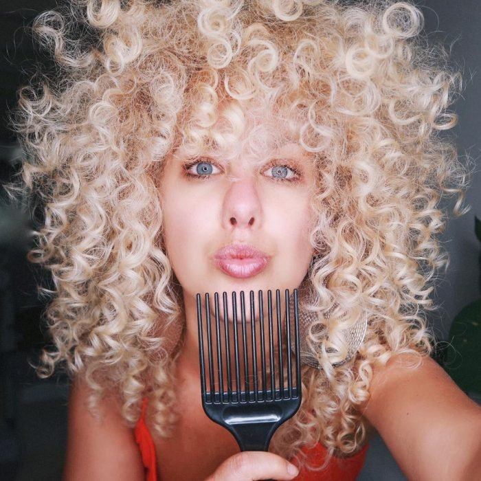 Chica de cabello chino y rubio cepillándoselo