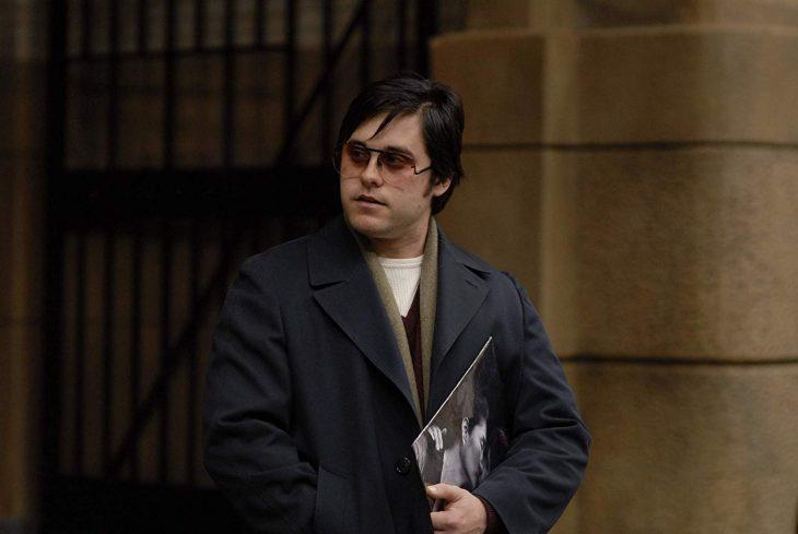 Hombre gordo con lentes y abrigo cargando un disco de acetato