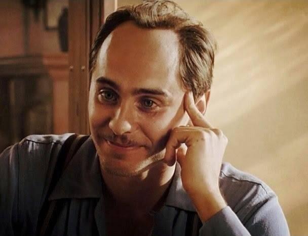 Hombre calvo y de bigote sonriendo recargado sobre su mano