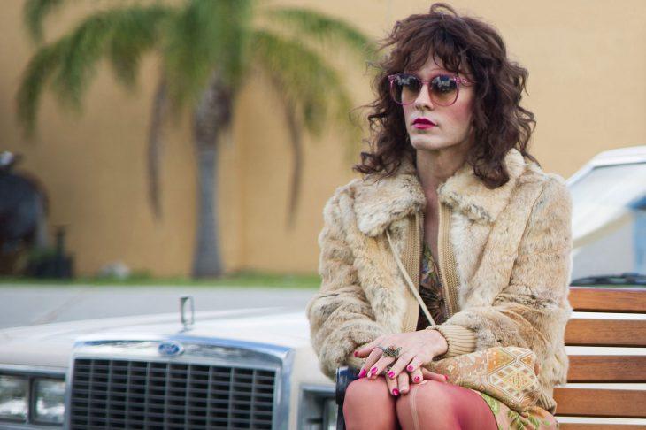 Hombre vestido de mujer con lentes y abrigo sentado en una banca de madera