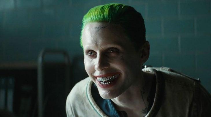 Hombre de cabello verde, dientes plateados y tatuajes en el rostro que está sonriendo