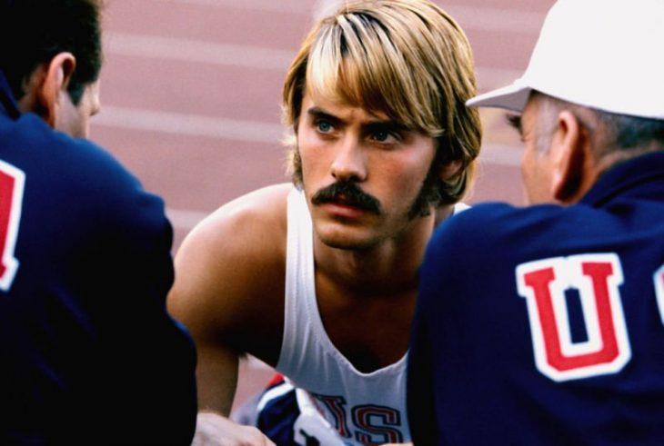 Hombre rubio y de bigote en una pista para correr mirando a otros dos hombres