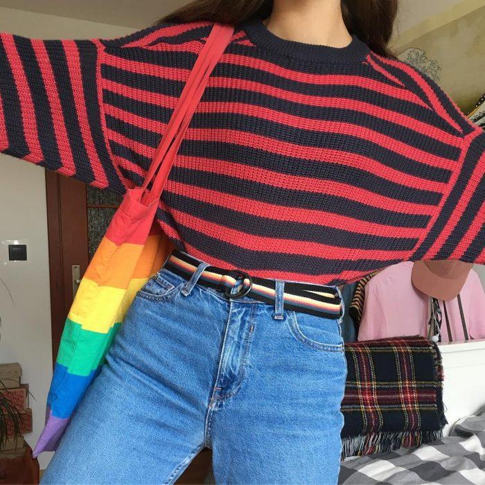 mujer con jeans a la cintura y sueter de rayas