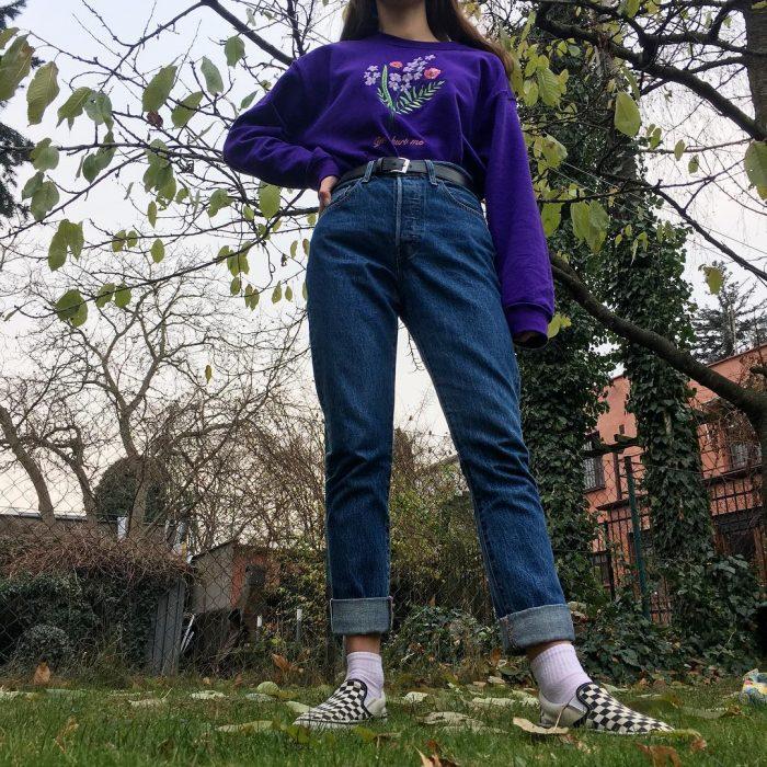 mujer con jeans de mezclilla y sudadera morada