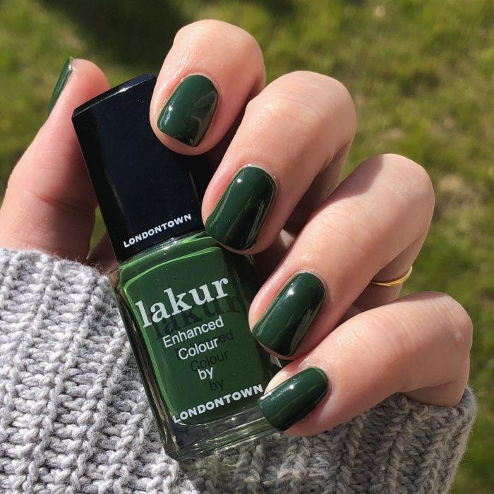 manos de mujer con uñas color verde