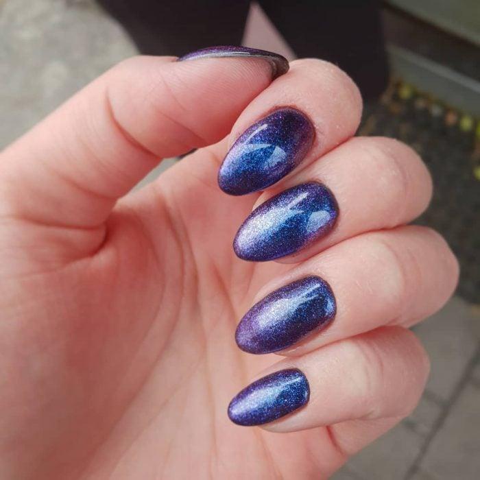 manos de mujer con uñas color azul metálico