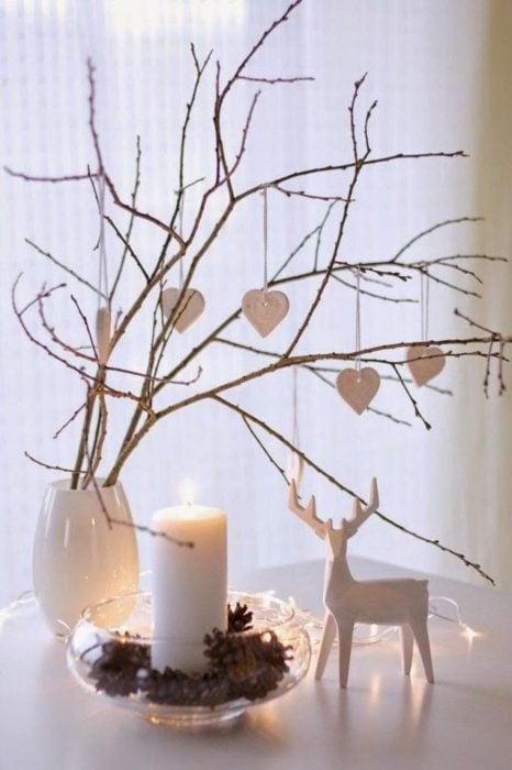 Florero con ramas secas, un venado y corazones