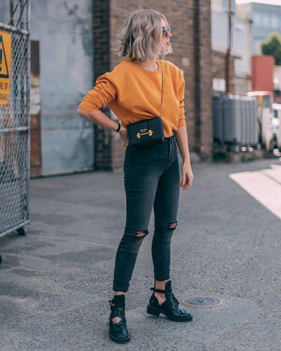 mujer rubia con suéter naranja
