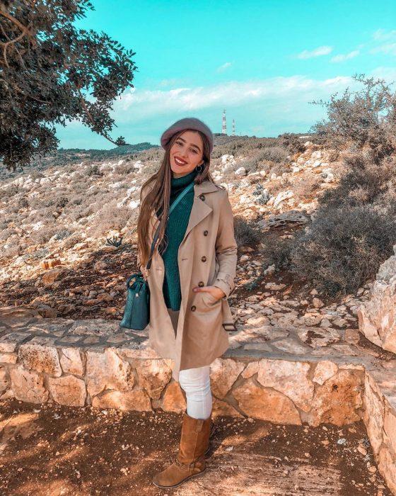 mujer con abrigo café y sueter verde