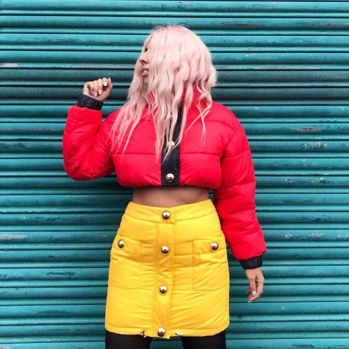 mujer con chamarra puffer crop top falda amarillo