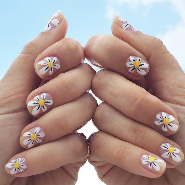manos de mujer con uñas y margaritas blancas