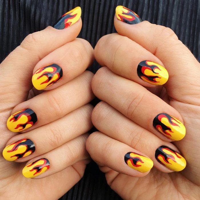 mujer con uñas de fuego con negro